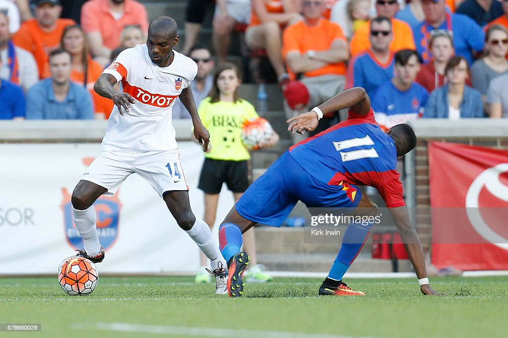 Omar Cummings of FC Cincinnati dribbles the ball past Wilfried Zaha of Crystal Palace FC during the first half at Nippert Stadium on July 16 2016 in...
