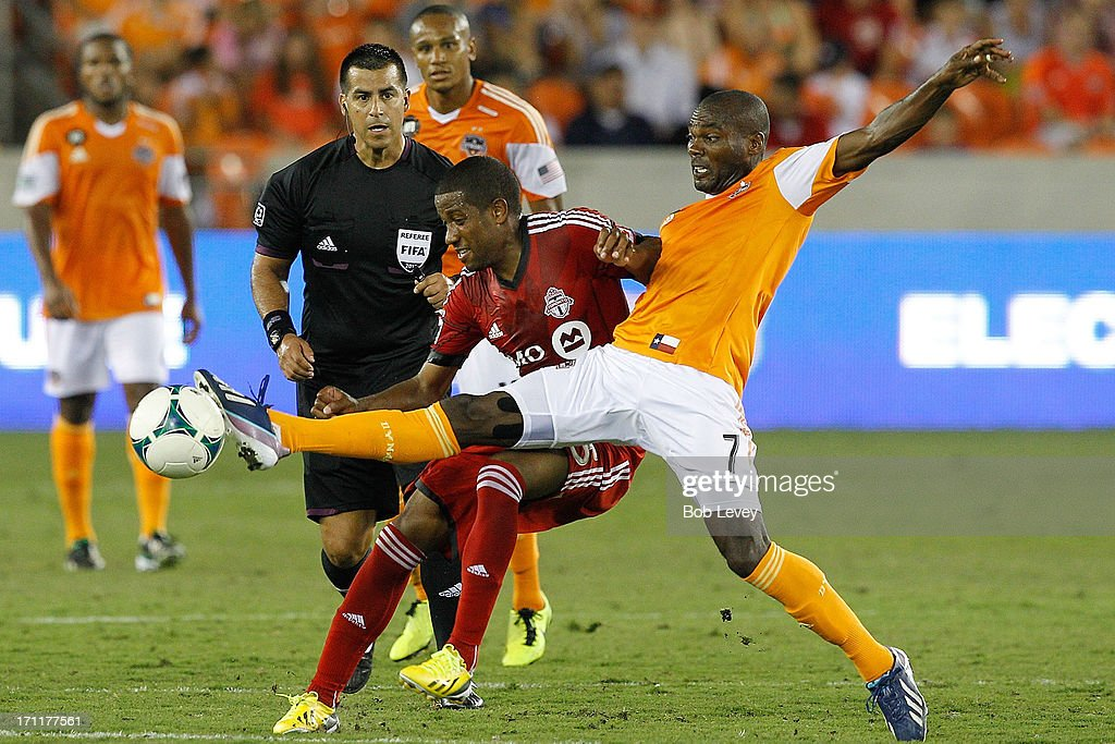 Omar Cummings #7 of Houston Dynamo reaches for the ball as Jeremy Hall #25 of Toronto FC defends in the second half at BBVA Compass Stadium on June 22, 2013 in Houston, Texas.