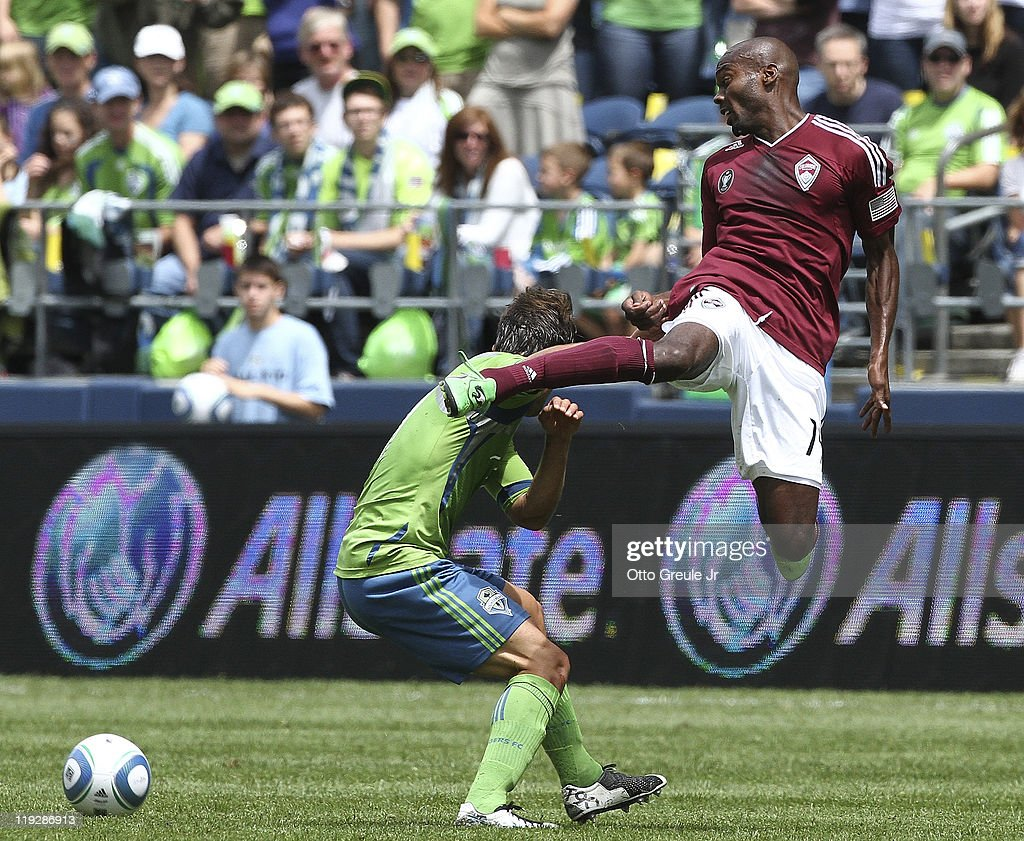 Omar Cummings of the Colorado Rapids battles Patrick Ianni of the Seattle Sounders FC at CenturyLink Field on July 16 2011 in Seattle Washington The...