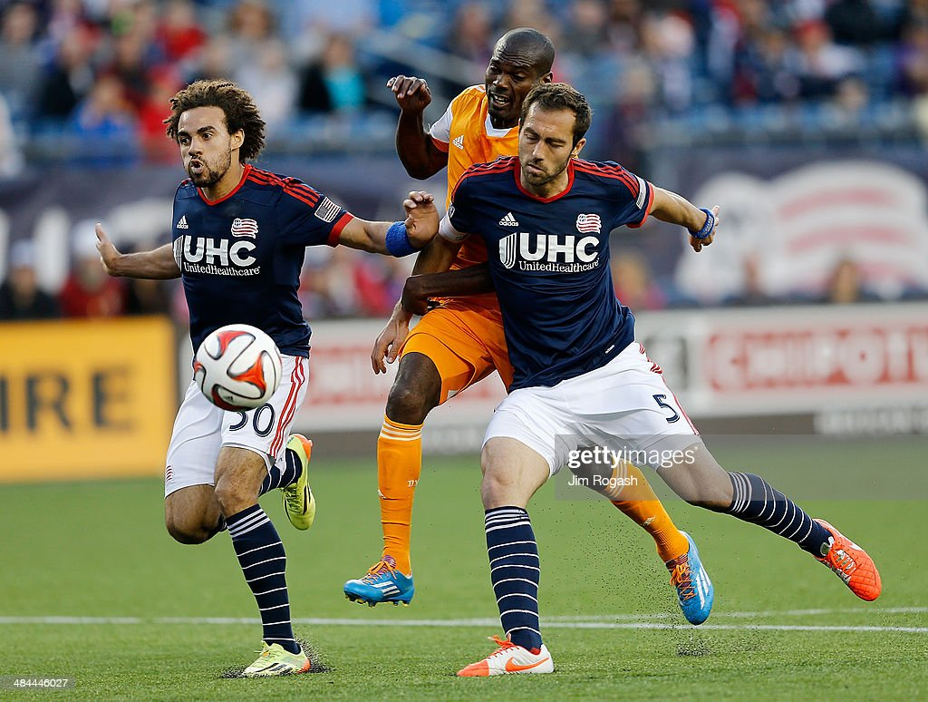 Omar Cummings of the Houston Dynamo is defended by Kevin Alston and AJ Soares in the 2nd half at Gillette Stadium on April 12 2014 in Foxboro...