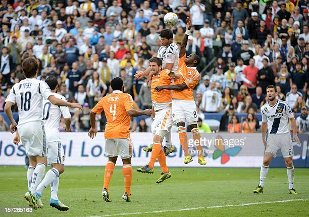 Omar Gonzalez of Los Angeles Galaxy heads in a goal over Bobby Boswell and Kofi Sarkodie of Houston Dynamo in the second half in the 2012 MLS Cup at...
