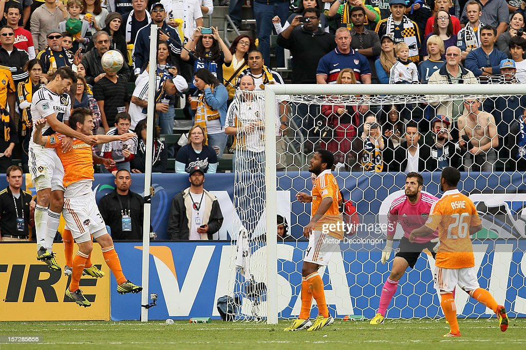 Omar Gonzalez #4 of Los Angeles Galaxy heads in a goal over Bobby Boswell #32 and Kofi Sarkodie #8 of Houston Dynamo in the second half in the 2012 MLS Cup at The Home Depot Center on December 1, 2012 in Carson, California.