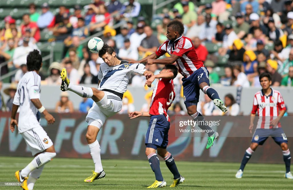 Omar Gonzalez of the Los Angeles Galaxy heads the corner kick as Jose Correa of Chivas USA grabs hold of Gonzalez's jersey in the second half during...