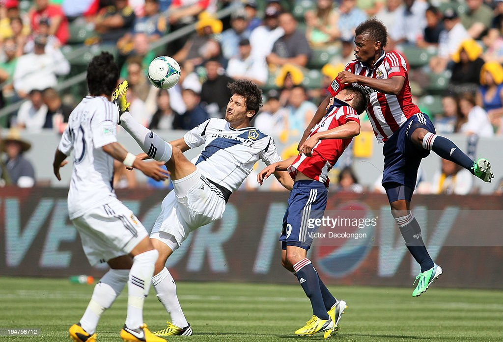 <a gi-track='captionPersonalityLinkClicked' href=/galleries/search?phrase=Omar+Gonzalez&family=editorial&specificpeople=2488485 ng-click='$event.stopPropagation()'>Omar Gonzalez</a> #4 of the Los Angeles Galaxy heads the corner kick as Jose Correa #27 of Chivas USA releases Gonzalez's jersey in the second half during the MLS match at The Home Depot Center on March 17, 2013 in Carson, California. Chivas USA and the Los Angeles Galaxy played to a 1-1 draw.