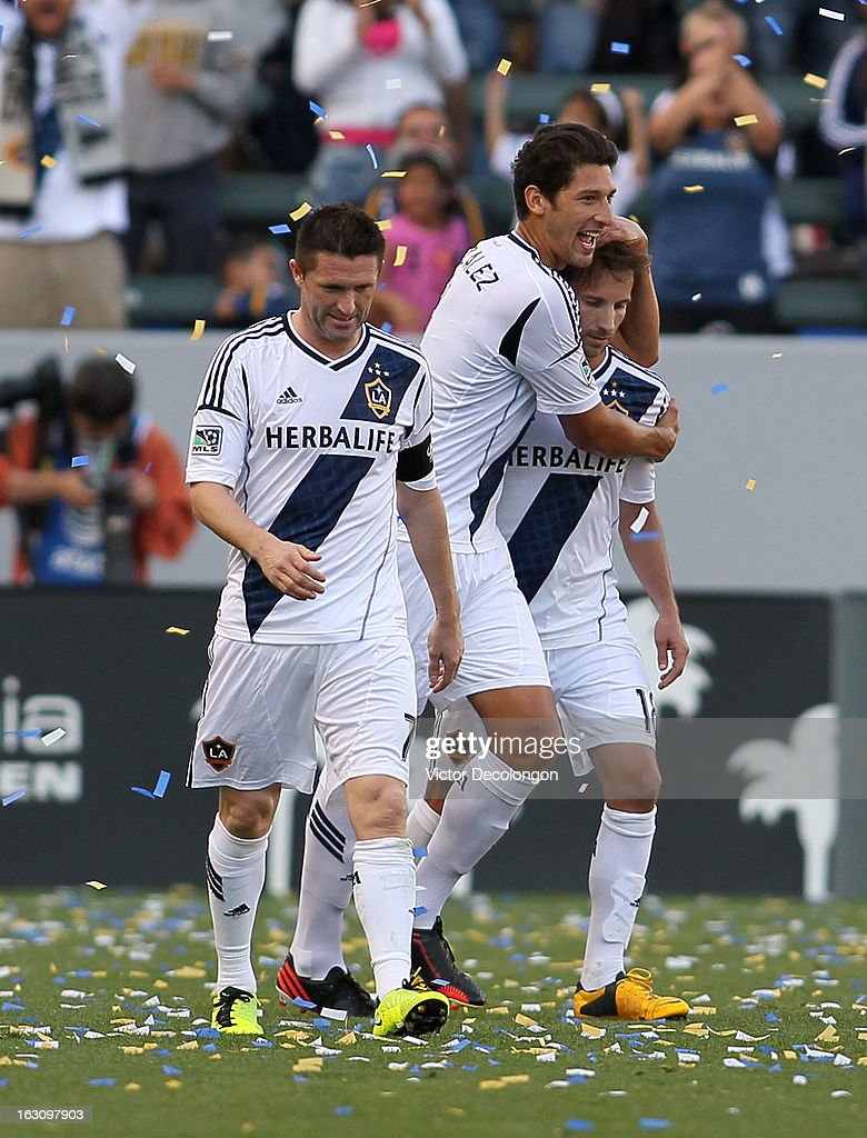 Omar Gonzalez #4 of the Los Angeles Galaxy hugs teammate Mike Magee #18 after Magee scored a goal in the second half as teammate Robbie Keane #7 looks on during the MLS match against the Chicago Fire at The Home Depot Center on March 3, 2013 in Carson, California. The Galaxy defeated the Fire 4-0.