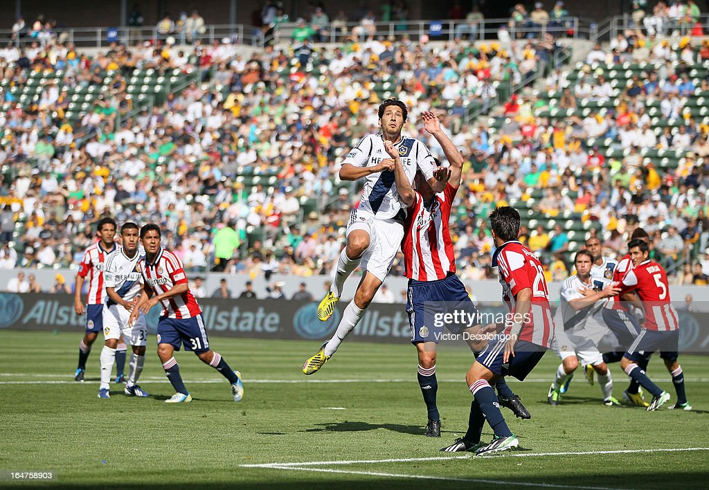 Omar Gonzalez #4 of the Los Angeles Galaxy jumps over Bobby Burling #2 of Chivas USA for the ball during the MLS match at The Home Depot Center on March 17, 2013 in Carson, California. Chivas USA and the Los Angeles Galaxy played to a 1-1 draw.