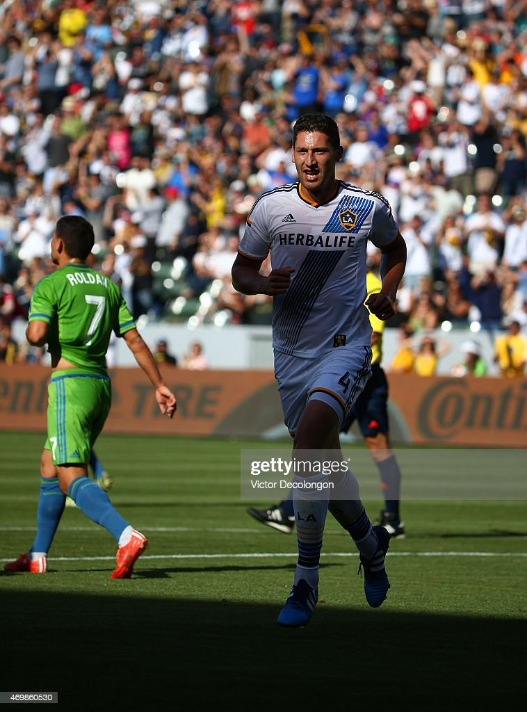 <a gi-track='captionPersonalityLinkClicked' href=/galleries/search?phrase=Omar+Gonzalez&family=editorial&specificpeople=2488485 ng-click='$event.stopPropagation()'>Omar Gonzalez</a> #4 of the Los Angeles Galaxy runs after teammate <a gi-track='captionPersonalityLinkClicked' href=/galleries/search?phrase=Alan+Gordon+-+Fu%C3%9Fballspieler&family=editorial&specificpeople=11667134 ng-click='$event.stopPropagation()'>Alan Gordon</a> #9 (not in photo) after Gordon scored a goal in the first half as Cristian Rolan #7 of Seattle Sounders FC looks on in the second half of their MLS match at StubHub Center on April 12, 2015 in Los Angeles, California. The Galaxy defeated the Sounders 1-0.