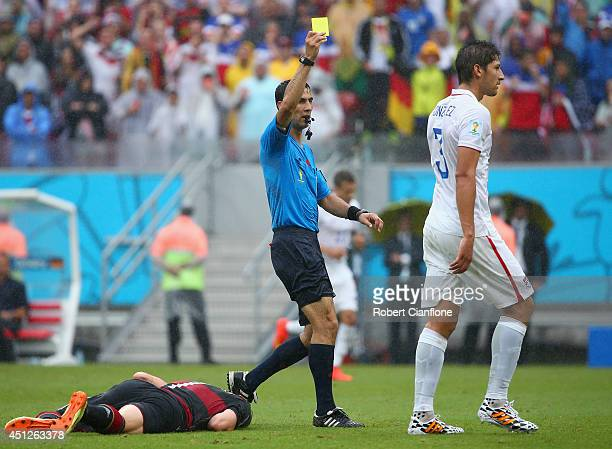 Omar Gonzalez of the United States is shown a yellow card by referee Ravshan Irmatov after a foul on Bastian Schweinsteiger of Germany during the...