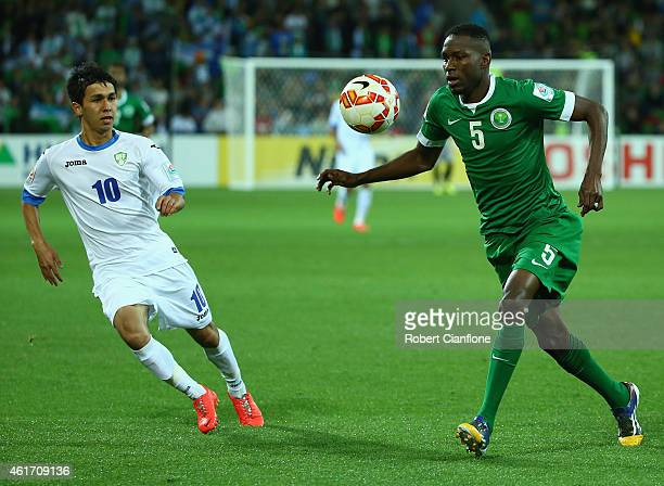 Omar Howsawi of Saudi Arabia is pressured by JamShid Iskanderov of Uzbekistan during the 2015 Asian Cup match between Uzbekistan and Saudi Arabia at...