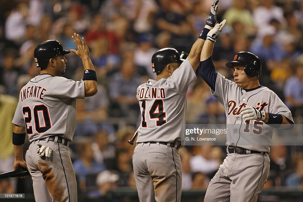 Omar Infante and Placido Polanco of Detroit greet Brandon Inge after the Tigers went ahead during action between the Detroit Tigers and Kansas City...