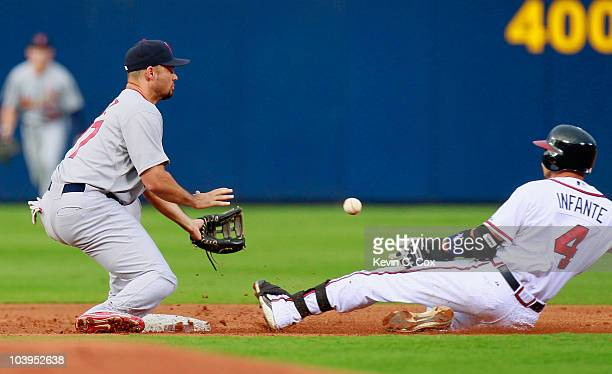 Omar Infante of the Atlanta Braves slides in a safely at second base as Pedro Feliz of the St Louis Cardinals misplays the throw at Turner Field on...
