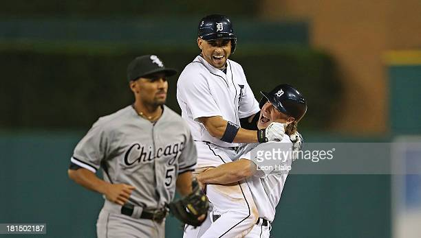 Omar Infante of the Detroit Tigers celebrates with teammate Andy Dirks after hitting an infield single scoring Don Kelly to win the game in the...