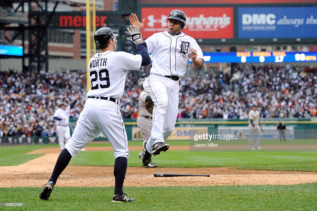 Omar Infante of the Detroit Tigers celebrates with teammate Danny Worth after Infante scored the gamewinning run on a RBI sacrifice fly hit by Don...