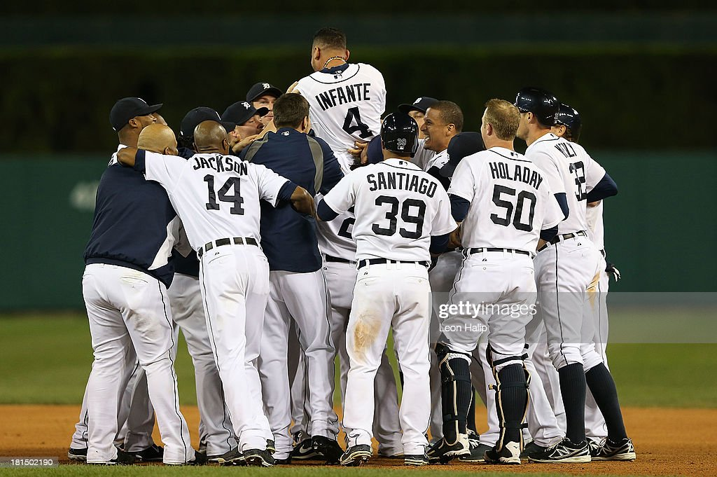 <a gi-track='captionPersonalityLinkClicked' href=/galleries/search?phrase=Omar+Infante&family=editorial&specificpeople=203255 ng-click='$event.stopPropagation()'>Omar Infante</a> #4 of the Detroit Tigers celebrates with teammates after hitting an infield single scoring Don Kelly #32 to win the game in the bottom of the 12th inning of the game against the Chicago White Sox at Comerica Park on September 21, 2013 in Detroit, Michigan. The TIgers defeated the White Sox 7-6.