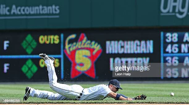 Omar Infante of the Detroit Tigers dives in an attempt to make the play on the gound ball hit into right field from Joe Mauer of the Minnestoa Twins...