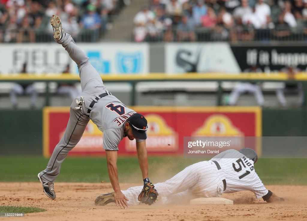 Omar Infante of the Detroit Tigers flips over Alex Rios of the Chicago White Sox while trying to turn a double play at US Cellular Field on September...
