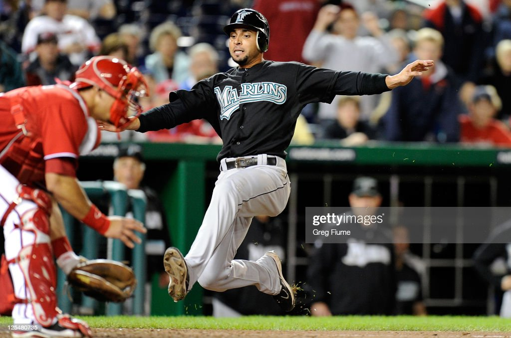 Omar Infante of the Florida Marlins scores in the 13th inning ahead of the throw to Wilson Ramos of the Washington Nationals at Nationals Park on...