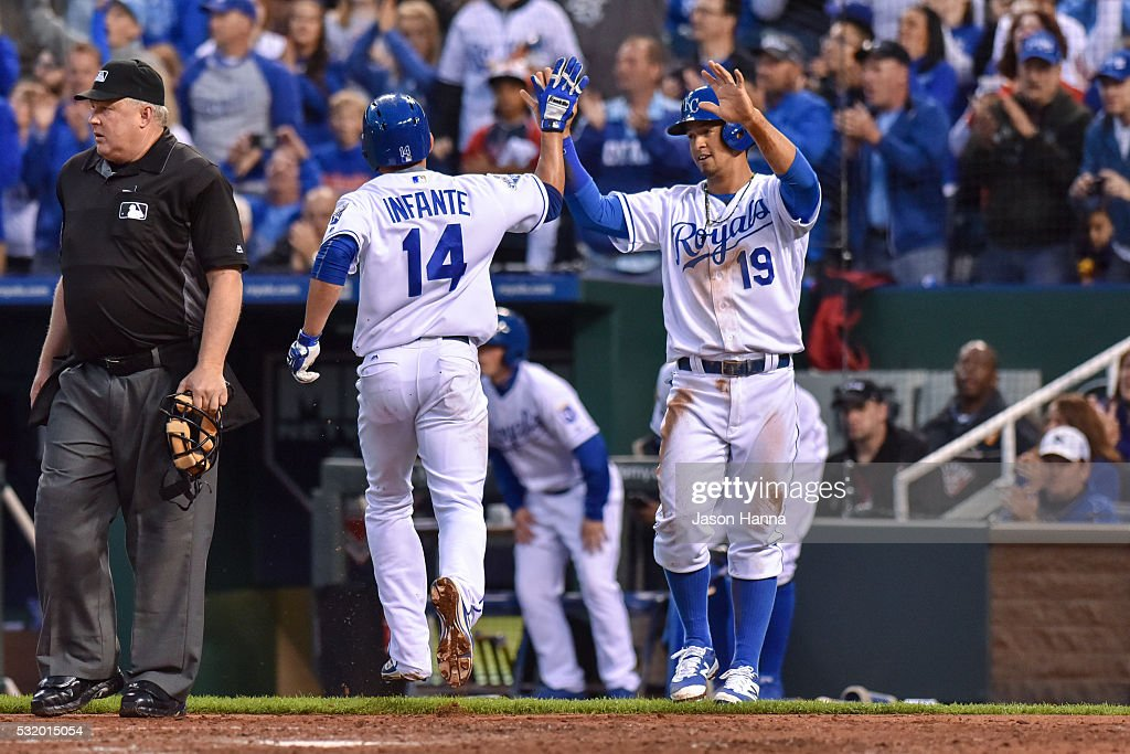 Omar Infante of the Kansas City Royals highfives teammate Cheslor Cuthbert after scoring the fourth and fifth runs of the game on a Paulo Orlando RBI...