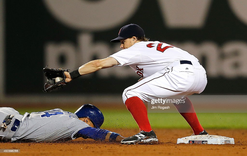 Omar Infante of the Kansas City Royals slides back to second base as Brock Holt of the Boston Red Sox takes a throw from the catcher in the fifth...