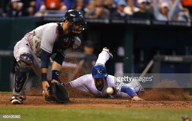 Omar Infante of the Kansas City Royals slides into home to score on a Billy Butler single as Yan Gomes of the Cleveland Indians fields the ball in...