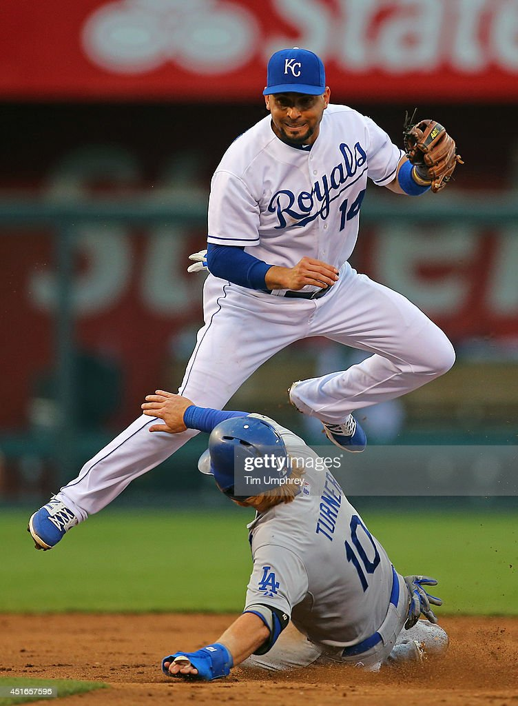 Omar Infante #14 of the Kansas City Royals turns a double play while jumping over Justin Turner #10 of the Los Angeles Dodgers in the third inning of a game at Kauffman Stadium on June 24, 2014 in Kansas City, Missouri. The Dodgers defeated the Royals 2-0.