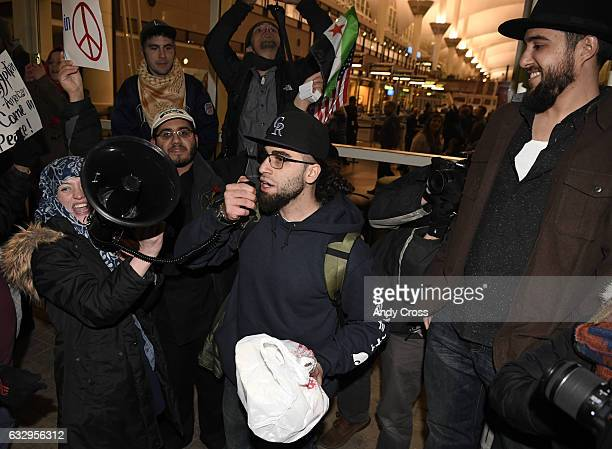 Omar Jawhar center from Lebanon addresses the crowd during an immigration protest at Denver International Airport in direct response to President...
