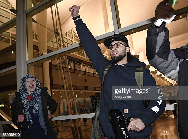 Omar Jawhar center right from Lebanon addresses the crowd during an immigration protest at Denver International Airport in direct response to...