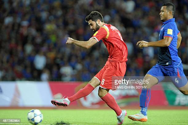 Omar Kharbin of Syria kicks the ball past Piseth of Cambodia during the 2018 World Cup qualifying football match between Cambodia and Syria in Phnom...
