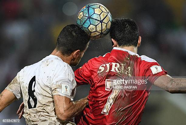 Omar Khrbin of Syria and Morteza Pouraliganji of Iran head the ball during the 2018 World Cup qualifying football match between Syria and Iran at...