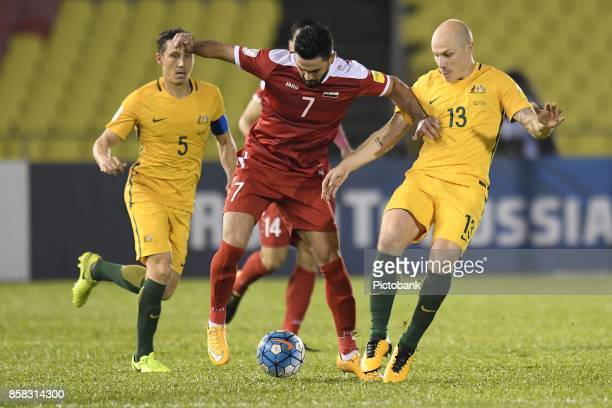 Omar Khrbin of Syria fights for the ball with Aaron Mooy of Australia during the FIFA 2018 World Cup Asian Playoff Leg 1 match between Syria and...