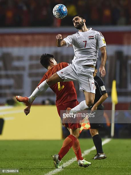 Omar Khrbin of Syria fights for the ball with China's Ren Hang during the 2018 World Cup qualifying group A match between Syria and China at Shanxi...