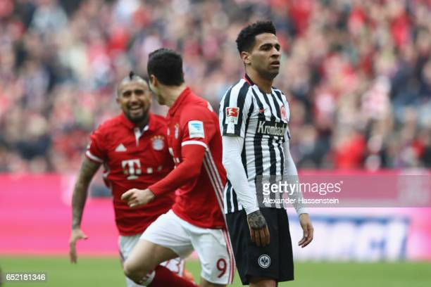 Omar Mascarell of Frankfurt reacts whilst Robert Lewandowski of Muenchen celebrates his 2nd team goal with his team mate Arturo Vidal during the...