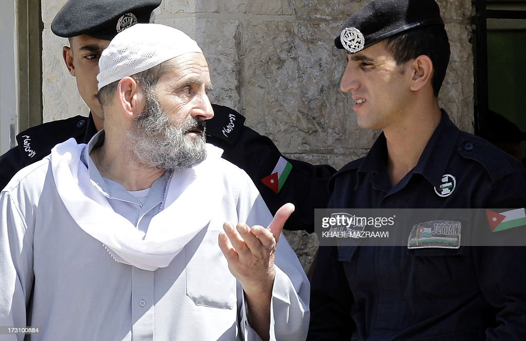 Omar Othman, the father of radical Islamist cleric Abu Qatada, speaks with Jordanian policemen outside the state security court in Amman on July 7, 2013. Abu Qutada pleaded not guilty to terror charges pressed by Jordanian military prosecutors just hours after his deportation from Britain, his lawyer said. Abu Qatada, who had been in and out of British prisons since 2002 even though he was never convicted of any offence, had once been described as now slain Al-Qaeda leader Osama bin Laden's right-hand man in Europe.