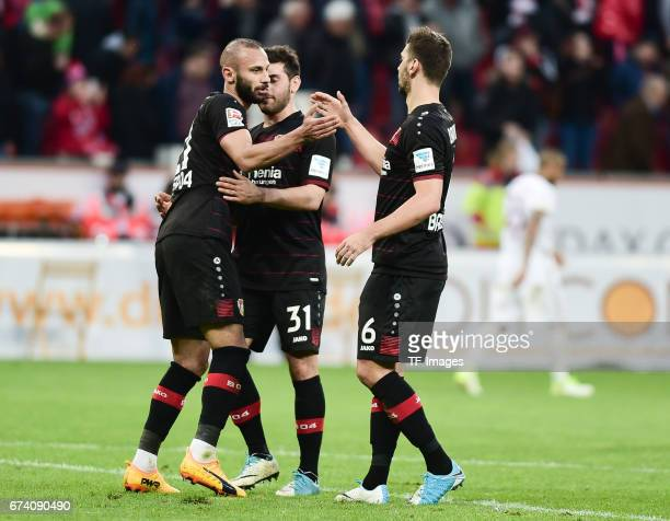 Omar Toprak of Leverkusen shakes hands with Kevin Volland of Leverkusen and Aleksandar Dragovic during the Bundesliga match between Bayer 04...