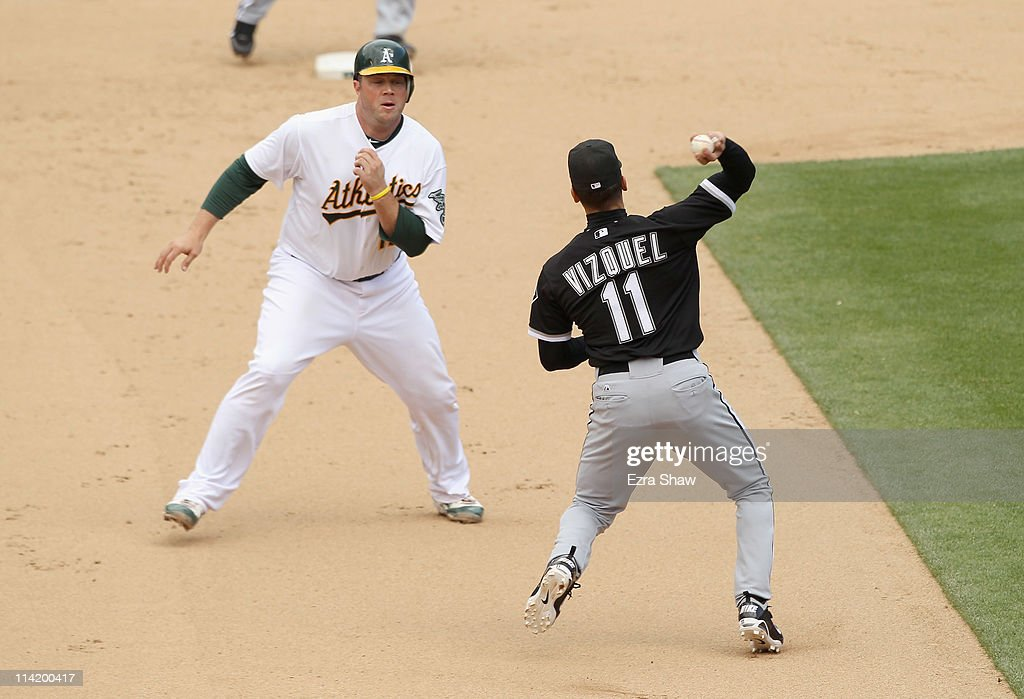 Omar Vizquel #11 of the Chicago White Sox throws around Landon Powell #11 of the Oakland Athletics to try to get a double play in the seventh inning at Oakland-Alameda County Coliseum on May 15, 2011 in Oakland, California. Powell scored later in the inning.