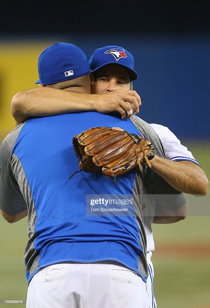 <a gi-track='captionPersonalityLinkClicked' href=/galleries/search?phrase=Omar+Vizquel&family=editorial&specificpeople=201489 ng-click='$event.stopPropagation()'>Omar Vizquel</a> #13 of the Toronto Blue Jays is embraced by <a gi-track='captionPersonalityLinkClicked' href=/galleries/search?phrase=Ricky+Romero&family=editorial&specificpeople=809221 ng-click='$event.stopPropagation()'>Ricky Romero</a> #24 after throwing out the first pitch before MLB game action against the Minnesota Twins on October 3, 2012 at Rogers Centre in Toronto, Ontario, Canada.