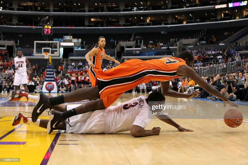 Omari Johnson of the Oregon State Beavers dives over Kevin Parrom of the Arizona Wildcats for the ball in the first half in the quarterfinals of the...