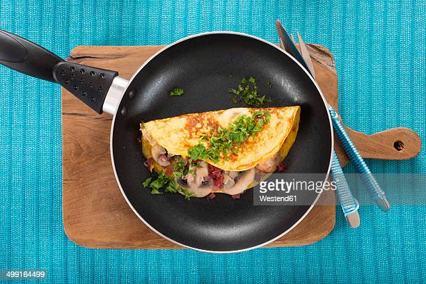 Omelette with champignon, onion and ham in frying pan