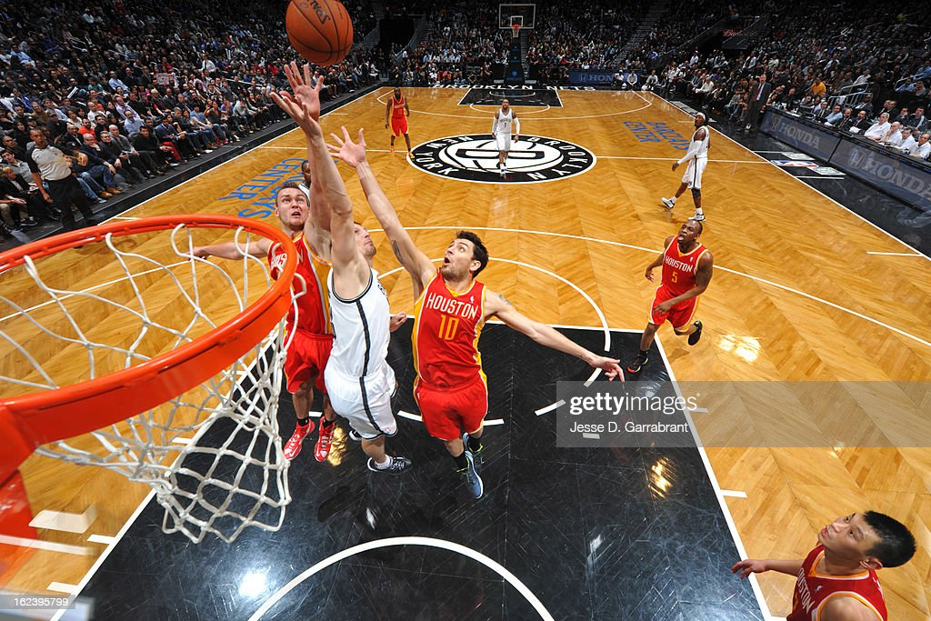 Omer Asik #3 and Carlos Delfino #10 of the Houston Rockets reach for a rebound against Mirza Teletovic #33 of the Brooklyn Nets at the Barclays Center on February 22, 2013 in Brooklyn, New York.