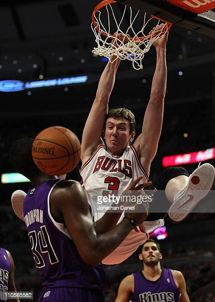 Omer Asik of the Chicago Bulls dunks the ball over Jason Thompson of the Sacramento Kings at the United Center on March 21 2011 in Chicago Illinois...
