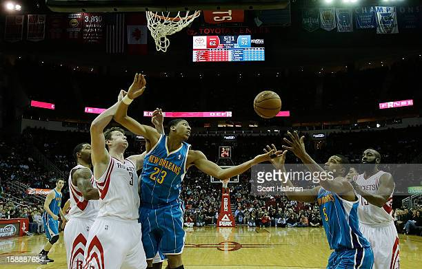 Omer Asik of the Houston Rockets battles for a rebound in front of Anthony Davis and Dominic McGuire of the New Orleans Hornets at Toyota Center on...
