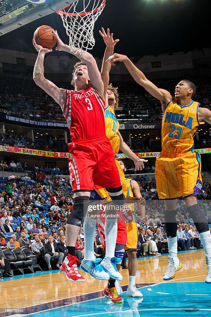 Omer Asik #3 of the Houston Rockets drives to the basket against Anthony Davis #23 and Robin Lopez #15 of the New Orleans Hornets on January 25, 2013 at the New Orleans Arena in New Orleans, Louisiana.