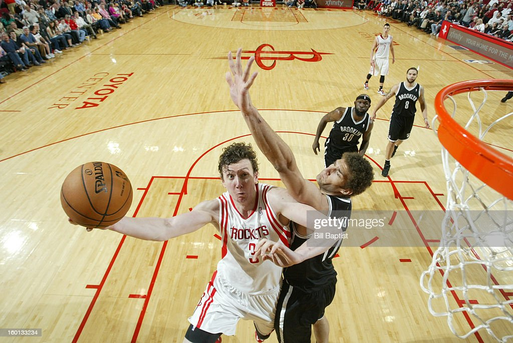 Omer Asik #3 of the Houston Rockets goes to the basket against Brook Lopez #11 of the Brooklyn Nets on January 26, 2013 at the Toyota Center in Houston, Texas.