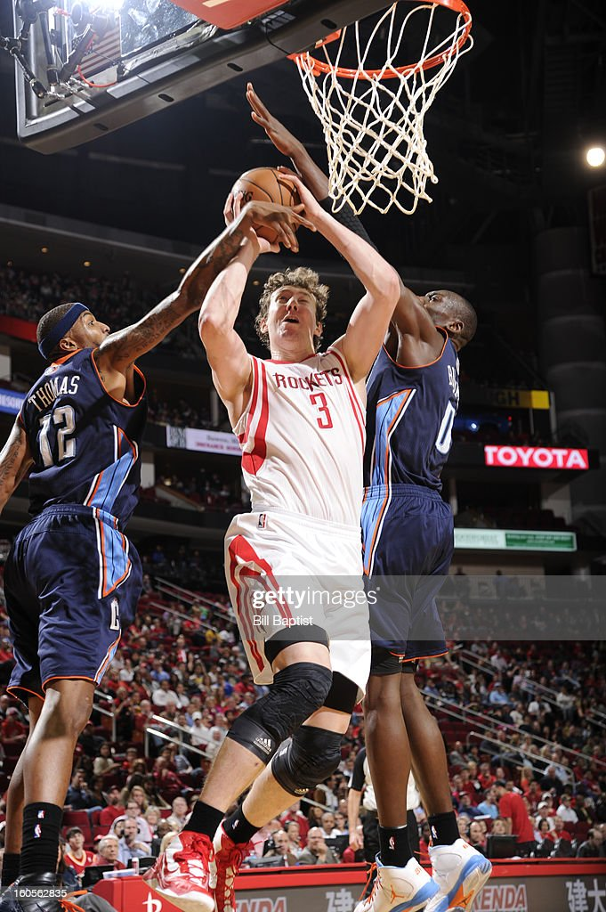 Omer Asik #3 of the Houston Rockets goes to the basket against Tyrus Thomas #12 and Bismack Biyombo #0 of the Charlotte Bobcats on February 2, 2013 at the Toyota Center in Houston, Texas.