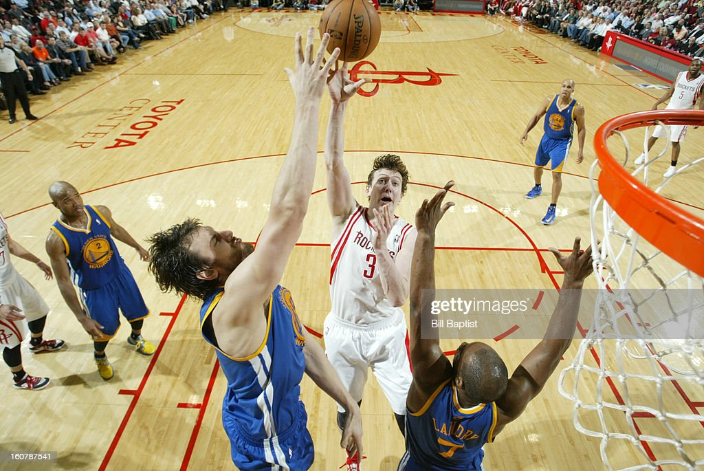 Omer Asik #3 of the Houston Rockets shoots the ball over Andrew Bogut #12 and Carl Landry #7 of the Golden State Warriors on February 5, 2013 at the Toyota Center in Houston, Texas.