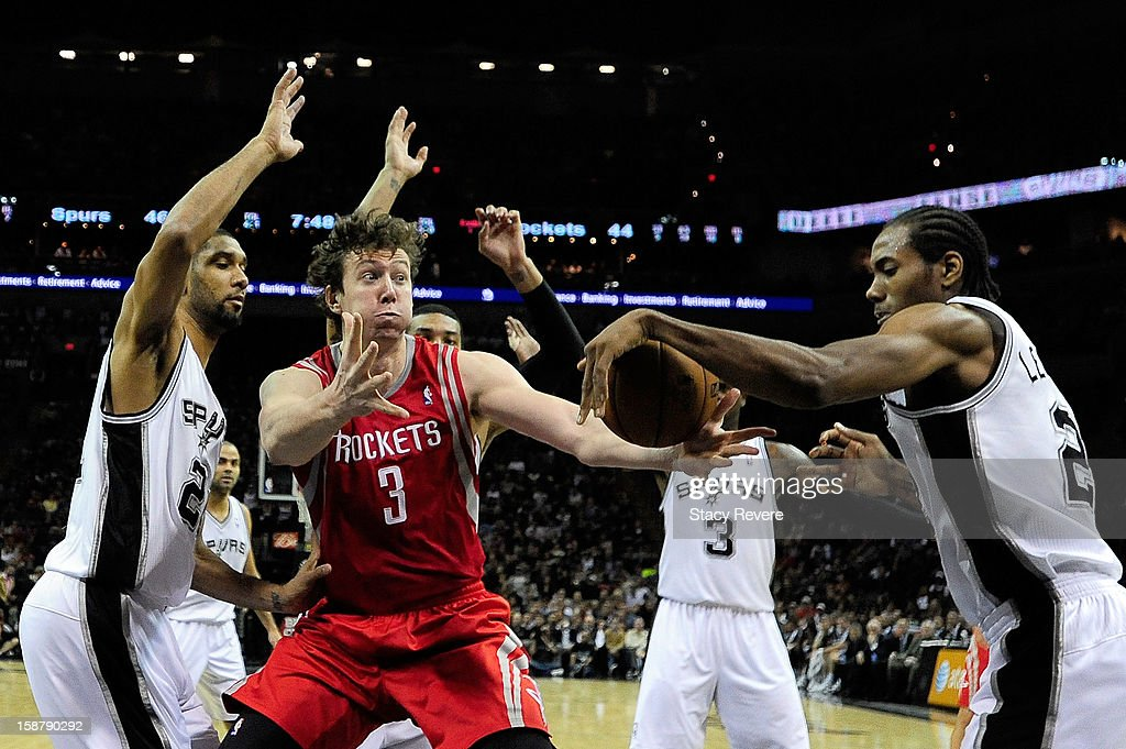 Omer Asik #3 of the Houston Rockets struggles for a loose ball with Kawhi Leonard #2 of the San Antonio Spurs during a game at AT&T Center on December 28, 2012 in San Antonio, Texas. San Antonio won the game 122-116.