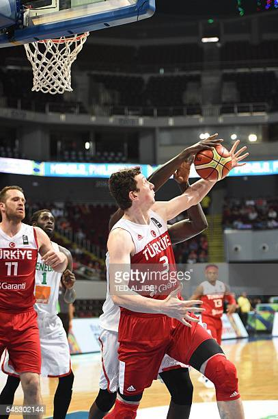 Omer Asik of Turkey fights for the ball with Cheik Mbodj of Senegal during their 2016 FIBA Olympic men's qualifying basketball tournament in Manila...