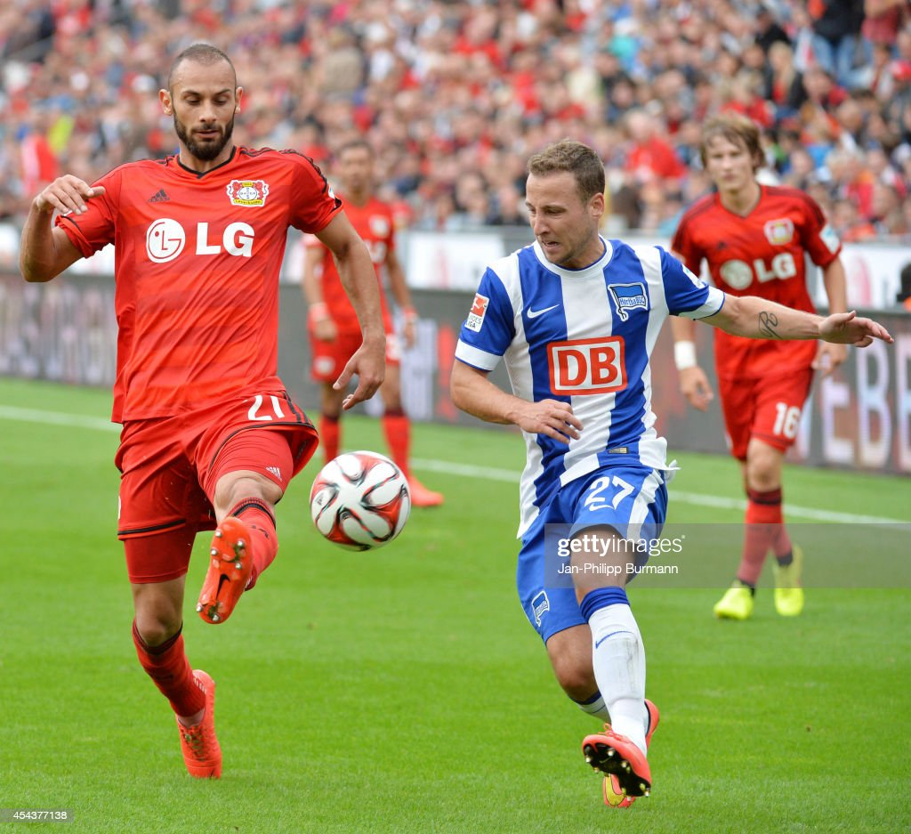 Omer Toprak of Bayer 04 Leverkusen und Roy Beerens of Hertha BSC compete for the ball during the Bundesliga match between Bayer 04 Leverkusen and Hertha BSC on August 30, 2014 in Leverkusen, Germany.