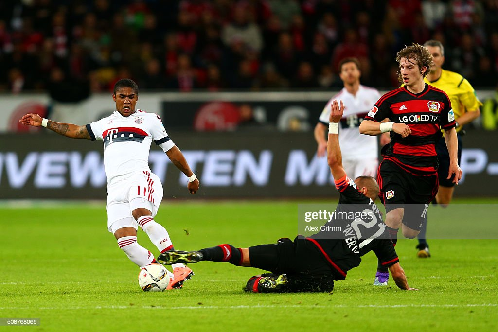 Omer Toprak of Bayer Leverkusen slides in on <a gi-track='captionPersonalityLinkClicked' href=/galleries/search?phrase=Douglas+Costa+-+Voetballer+-+Aanvaller+-+Geboren+1990&family=editorial&specificpeople=5672410 ng-click='$event.stopPropagation()'>Douglas Costa</a> of FC Bayern Muenchen during the Bundesliga match between Bayer Leverkusen and FC Bayern Muenchen at BayArena on February 6, 2016 in Leverkusen, Germany.