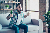 Omg! Goal! Crazy funny happy excited astonished amazed guy clothed in checkered shirt and jeans, he is eating pizza and drinking beer, sitting on a sofa and watching final of sport game